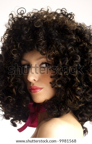 Woman wearing a huge afro wig. Model in a big afro wig