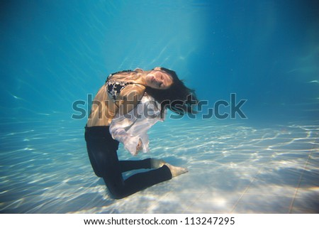 Woman wearing a jeans underwater in swimming pool - stock photo