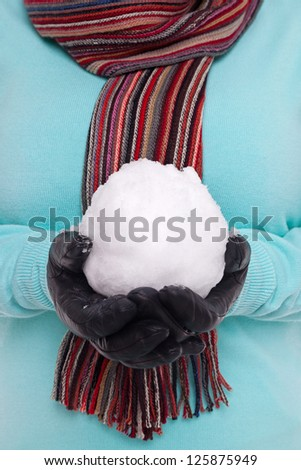 Woman wearing a knitted scarf and gloves holding a snowball. - stock photo