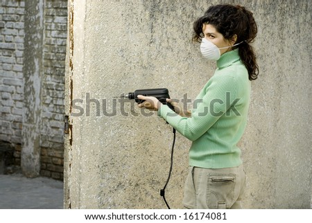 Woman wearing a mask using an electric sander. Horizontally framed photo. - stock photo