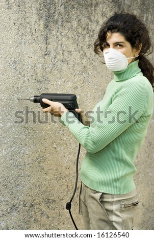 Woman wearing a paint mask on her face and holding a drill. Vertically framed photo. - stock photo