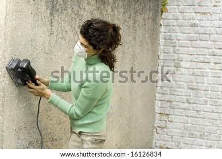 Woman wearing a painter's mask using a sander on a wall. Horizontally framed photo. - stock photo