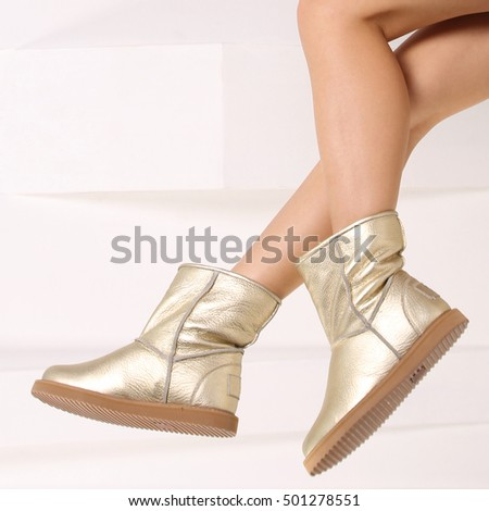 Woman wearing a pair of winter shoes. Fashionable shoe products. Women's shoes wearing on his feet.