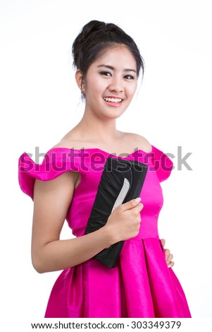Woman wearing a pink dress holding a black bag on a white background.