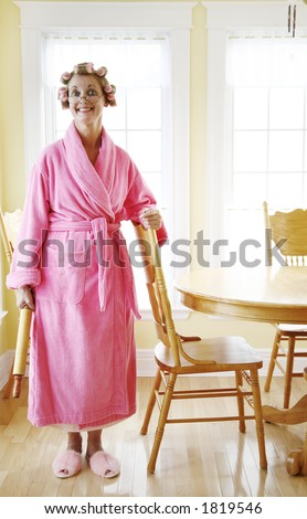 Woman wearing a pink robe and rollers in her dining room - stock photo