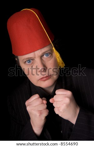 Woman wearing a red shriners fez over a black background - stock photo