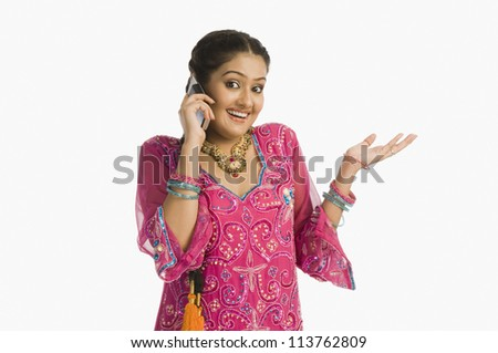Woman wearing a salwar kameez and talking on a mobile phone - stock photo