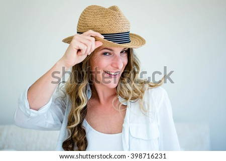 woman wearing a straw fedora, holding the rim of her hat and staring into the distance while smiling - stock photo