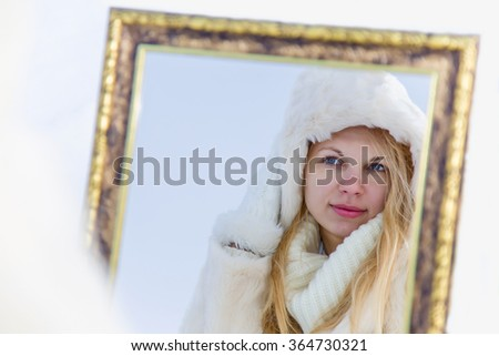 Woman wearing a white fur coat looking at her self in a mirror. She is trying on a white fur coat and deciding on an outfit. She looks fashionable and stylish. - stock photo