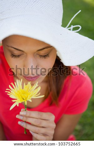 Woman wearing a white hat while smelling a yellow flower while looking down at the flower,
