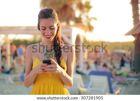 Woman wearing a yellow dress, using her smartphone - stock photo