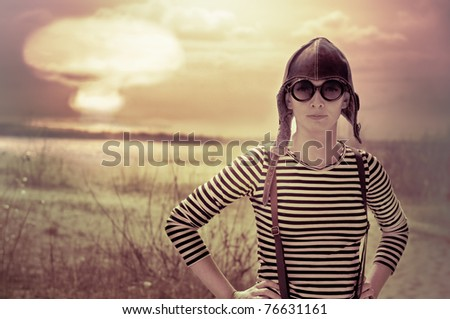 woman wearing aviator hat posing front of nuclear explosion - stock photo
