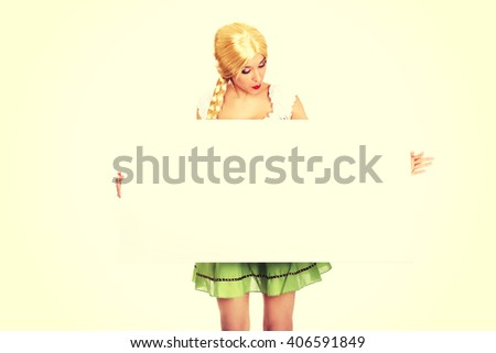 Woman wearing Bavarian dress holding empty banner. - stock photo