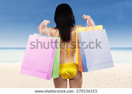 Woman wearing bikini carrying  shopping bags at beach - stock photo