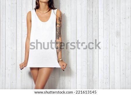 Woman wearing blank sleeveless t-shirt. Wood wall background. - stock photo
