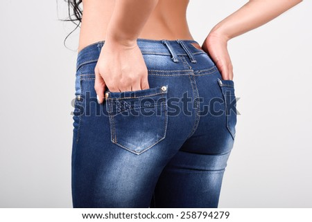 Woman wearing blue jeans with a beautiful waist. Studio shot - stock photo