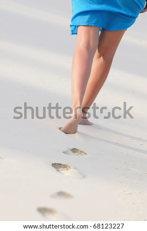 Woman wearing blue sarong walks along the beach. - stock photo