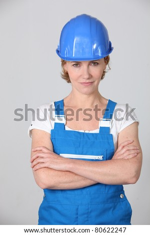 Woman wearing blue work overalls and hard hat - stock photo