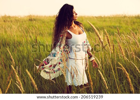 woman wearing boho style clothes in the field , hot summer day, retro colors - stock photo