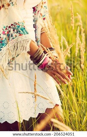woman wearing boho style clothes touching grass, hand with lot of braceletes, summer day in the field, retro colors - stock photo
