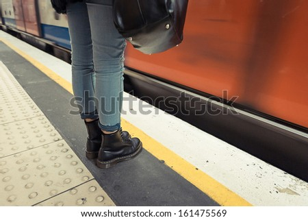 Woman Wearing Boots Waiting for Metro Train - stock photo