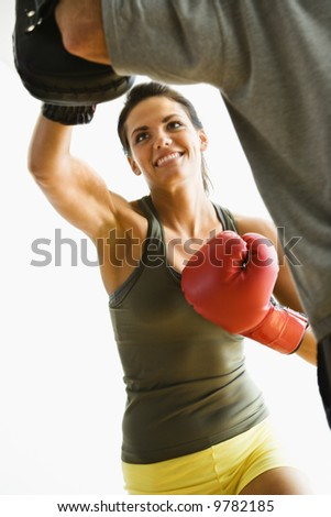 Woman wearing boxing gloves hitting training mits man is holding. - stock photo