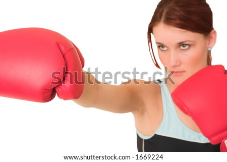 Woman wearing boxing gloves.  Looking serious. Shallow d.o.f  -  face out of focus, gloves in focus.