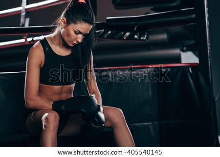 woman wearing boxing gloves sitting near ring - stock photo