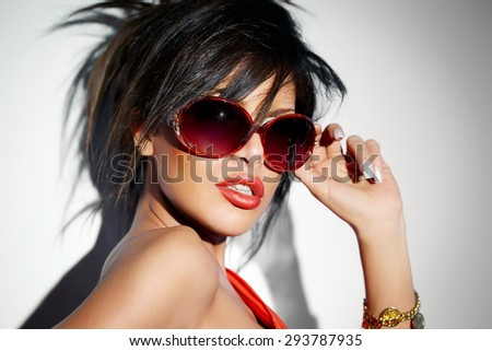 Woman wearing bright red sunglasses, lipstick and dress.