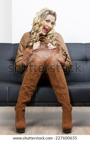 woman wearing brown clothes and boots with a handbag sitting on sofa - stock photo