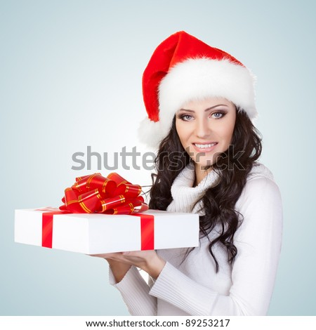 woman wearing christmas hat and holding gift box