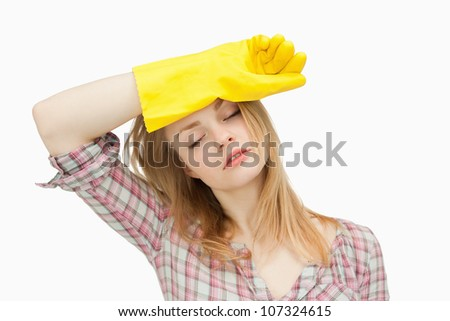 Woman wearing cleaning gloves while wiping her brow against white background - stock photo