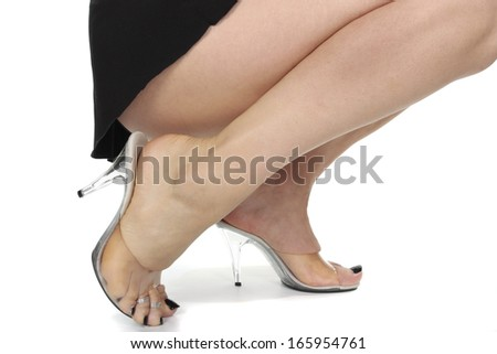 Woman wearing  clear  high heel shoes over white background