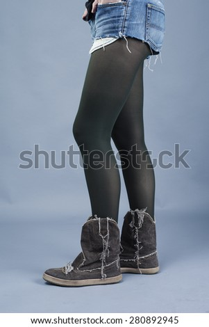 Woman wearing cowboy boots, stockings and denim shorts. long legs - stock photo