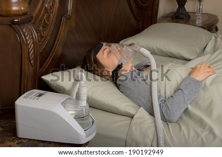 Woman wearing CPAP machine for sleep apnea - stock photo