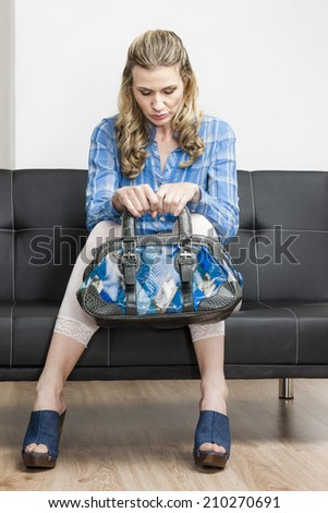 woman wearing denim clogs with a handbag sitting on sofa - stock photo