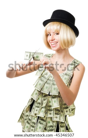 Woman wearing dress made of dollars cut dollar using scissors