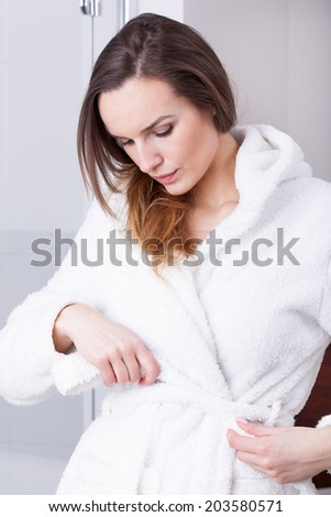 Woman wearing dressing-gown in the bathroom, vertical
