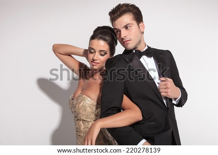Woman wearing elegant dress holding her lover arm, looking down, while the man is ajusting his jacket. - stock photo