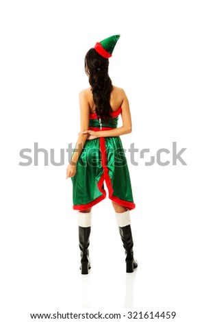 Woman wearing elf clothes standing back to camera. - stock photo