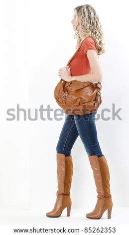 woman wearing fashionable brown boots with a handbag