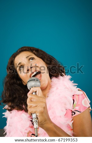 Woman wearing feather boa singing into microphone - stock photo