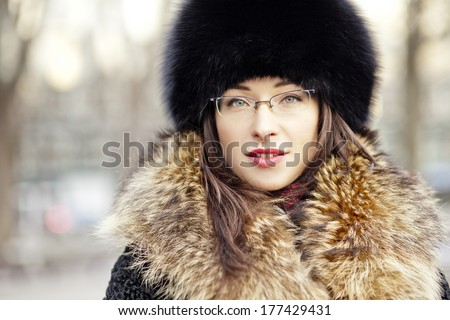 Woman wearing fur hat and glasses - stock photo