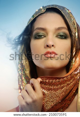 Woman wearing glamorous make up and sequin hoodie - stock photo