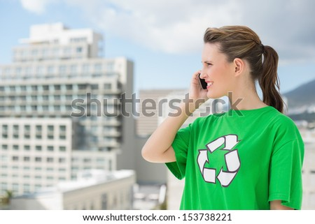 Woman wearing green recycling tshirt talking on the phone outside on a sunny day - stock photo