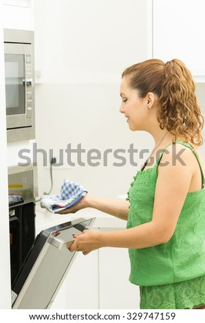Woman wearing green top in modern kitchen holding mittens and opening oven door.