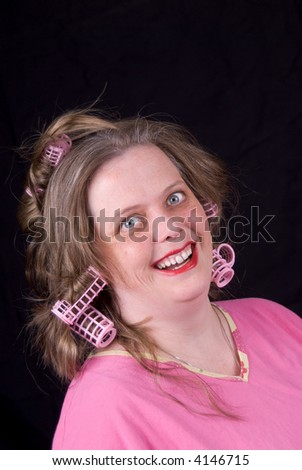 Woman wearing hair curlers and extreme makeup making a funny face isolated over black - stock photo