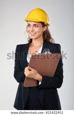 Woman wearing hardhat safety helmet recording information on clipboard, architect surveyor engineer professional - stock photo