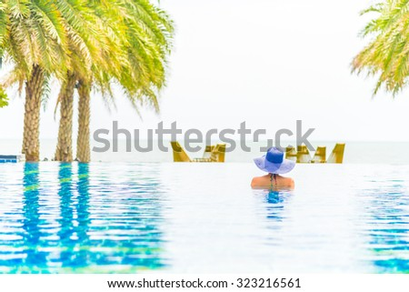 Woman wearing hat in the hotel pool resort - stock photo