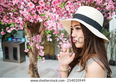 woman wearing hat portrait with replica sakura tree - stock photo